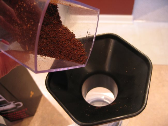 add coffee grounds into aeropress coffee brewer with funnel